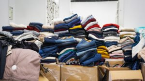 Stock clothing - A collection jeans, sweaters, jackets in modern distribution warehouse in the mall. Inventory, logistic, export concept. Foto: WCRS Ltd.
